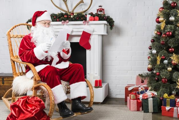 Santa che si siede sulla sedia a dondolo vicino all'albero di natale Foto Premium