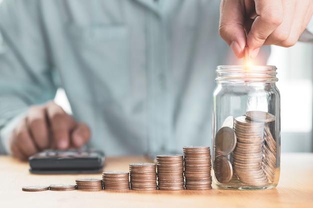 Risparmia denaro e concetto di investimento, uomo d'affari che mette moneta al barattolo di risparmio con monete impilate e utilizza la calcolatrice, Foto Premium