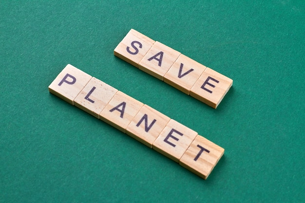 Salvare il concetto di pianeta. preoccupazione ambientale e risparmio della terra. cubi di legno con lettere isolate su sfondo verde. Foto Premium