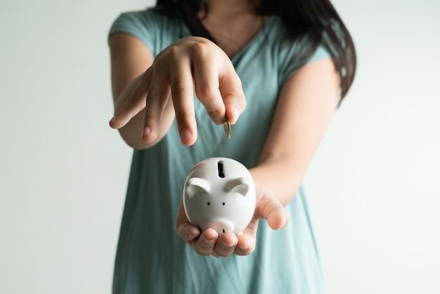 Concetto di affari e di risparmio, ragazza sveglia con il porcellino salvadanaio e monete a casa Foto Premium