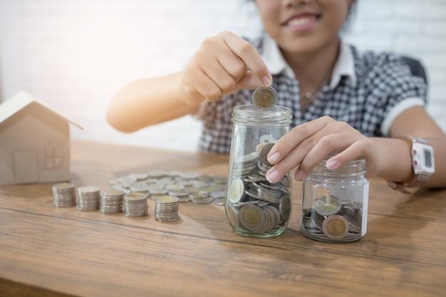 Risparmio di denaro e finanze concetto con la ragazza che mette le monete in vetro brocca Foto Premium