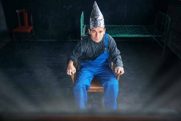Uomo spaventato in cappello di lamina di alluminio si siede sulla sedia e guarda la tv, concetto di paranoia. ufo, teoria del complotto, protezione dal furto di cervello, fobia Foto Premium