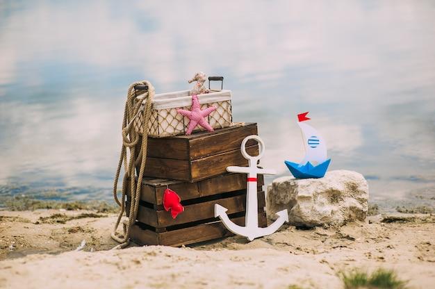 Scenario e dettagli in stile nautico sulla spiaggia di sabbia. temi marini. scatole di legno, ancora, barca, parti di fabbrica e corda da mare Foto Premium