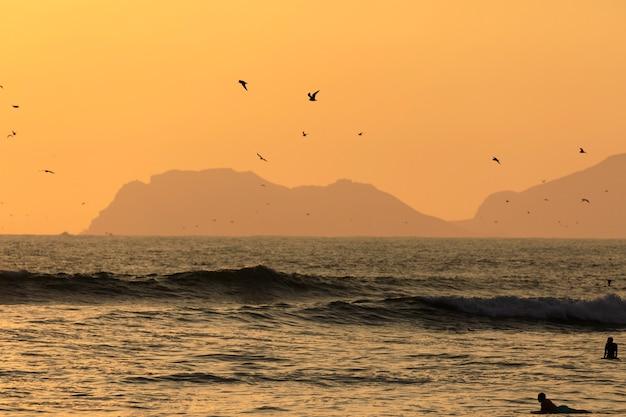 Momento scenico di tramonto con le siluette dei surfisti e dei gabbiani sulla spiaggia dell'oceano pacifico a lima, perù Foto Premium