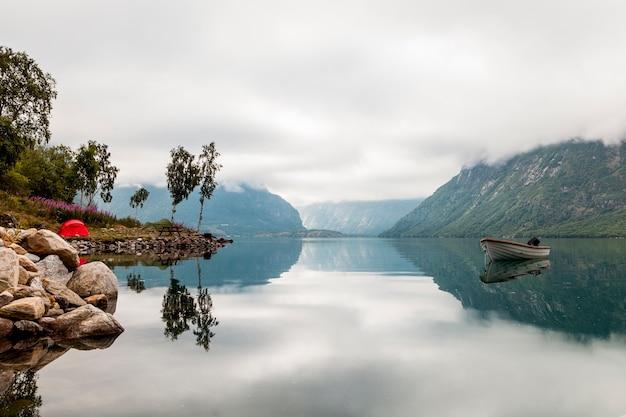 Vista panoramica della barca solitaria sul lago idilliaco Foto Premium