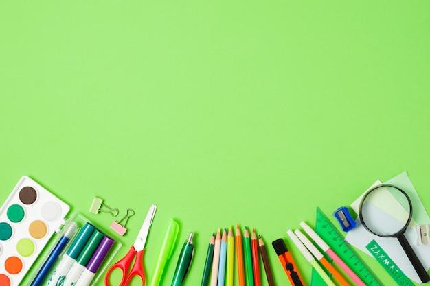 Disposizione degli accessori della scuola su fondo verde Foto Premium
