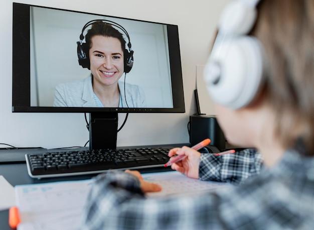 Scolaro prendendo corsi online con l'insegnante Foto Premium