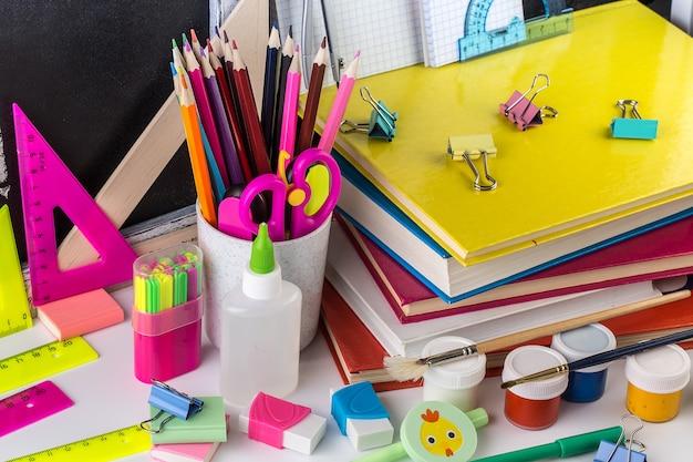 Cartoleria della scuola su un tavolo davanti alla lavagna Foto Premium