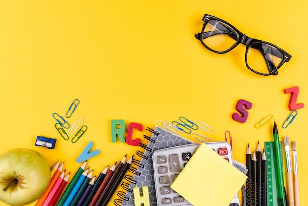Rifornimenti e occhiali di scuola su giallo Foto Premium