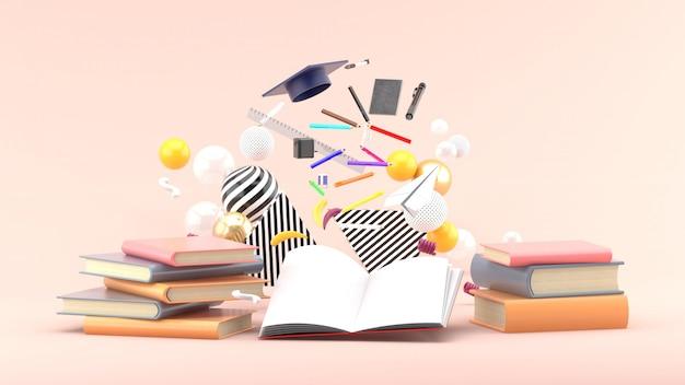 Materiale scolastico galleggiante da un libro tra palline colorate su rosa tenue. rendering 3d Foto Premium