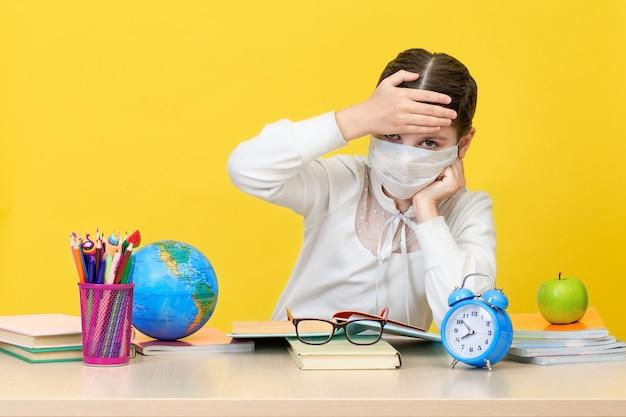 La studentessa alla sua scrivania in una mascherina medica su sfondo giallo. il concetto di istruzione domiciliare durante la quarantena. di nuovo a scuola. il nuovo anno scolastico. concetto di educazione del bambino. Foto Premium