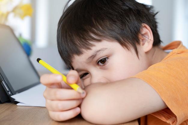 Scolaro in auto-isolamento utilizzando la tavoletta per i compiti, bored child faccia triste sdraiato a testa in giù guardando fuori nel profondo del pensiero, Foto Premium