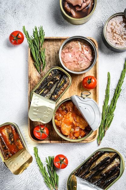 Spuntini di pesce: sardine in scatola, cozze, polpo, salmone e tonno. sfondo grigio. Foto Premium