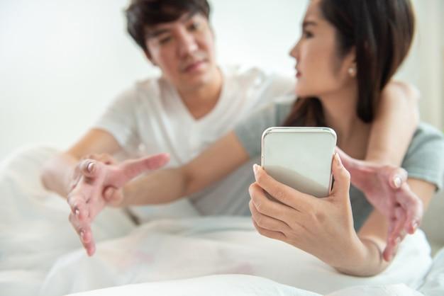 Ascoltare segretamente la conversazione al telefono o sbirciare post sociali, messaggi. il giovane asiatico e la donna litigano sul telefono cellulare intelligente con il concetto di relazione di argomento Foto Premium