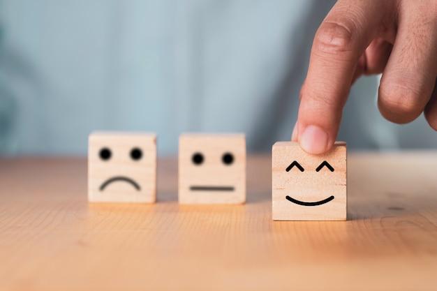 Seleziona il concetto di emozione o umore, mano che tiene la faccia sorridente o la faccia felice che stampa la schermata sul blocco di cubo di legno. Foto Premium