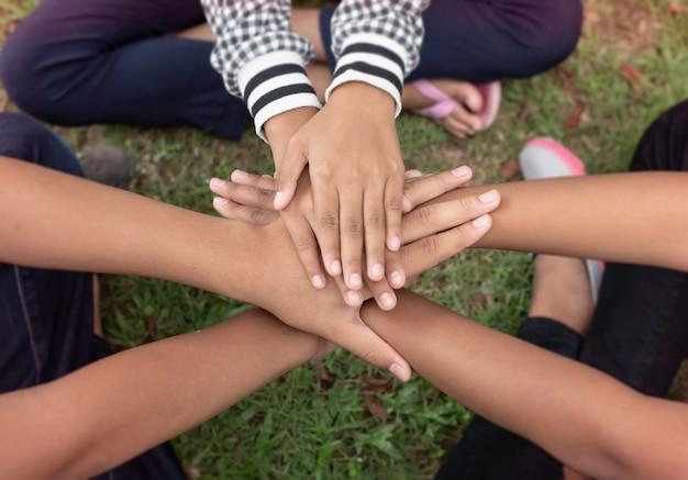 Nel fuoco selettivo delle mani dei bambini piccoli impilate insieme, amicizia, collaboratore, unità, segno di successo e potere, luce sfocata intorno Foto Premium