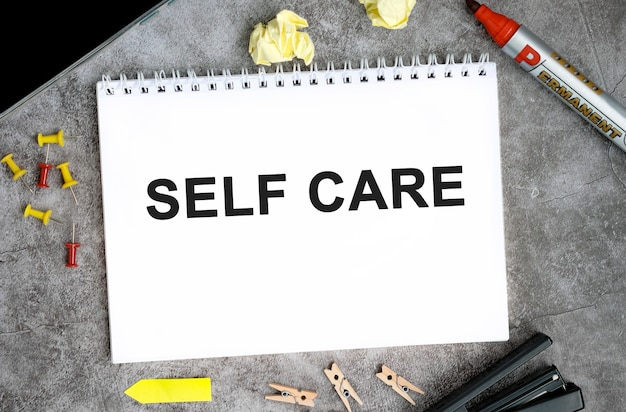 Testo di cura di sé su un taccuino bianco con spilli, pennarello e cucitrice su un tavolo di cemento Foto Premium