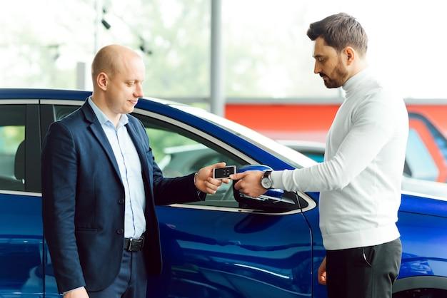 Il venditore e l'acquirente nel salone dell'auto Foto Premium