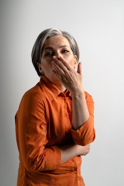 L'invio di aria baci donna dai capelli grigi abbastanza matura che indossa camicia arancione sorridente felicemente sul davanti Foto Premium