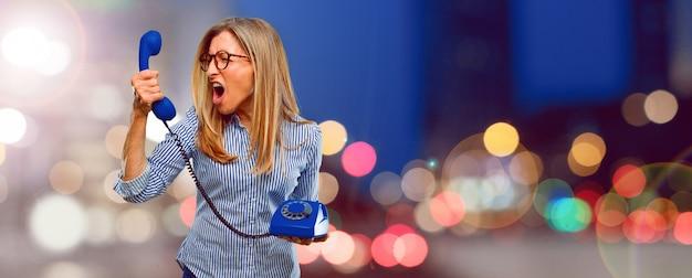 Senior bella donna con un telefono vintage Foto Premium