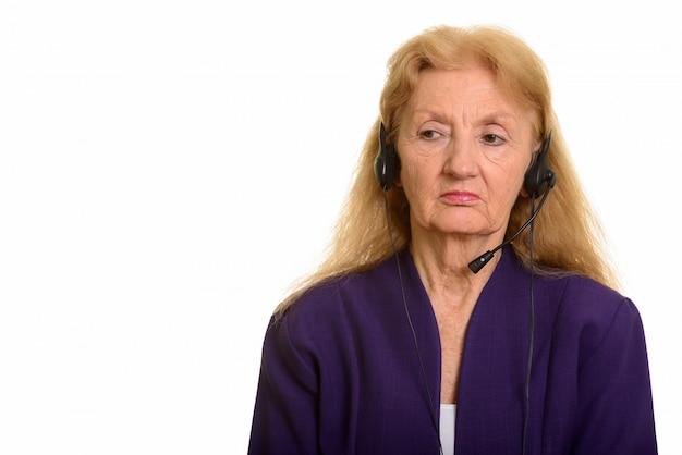 Cuffie d'uso della donna di affari senior che sembrano lavoro stanco nella call center Foto Premium