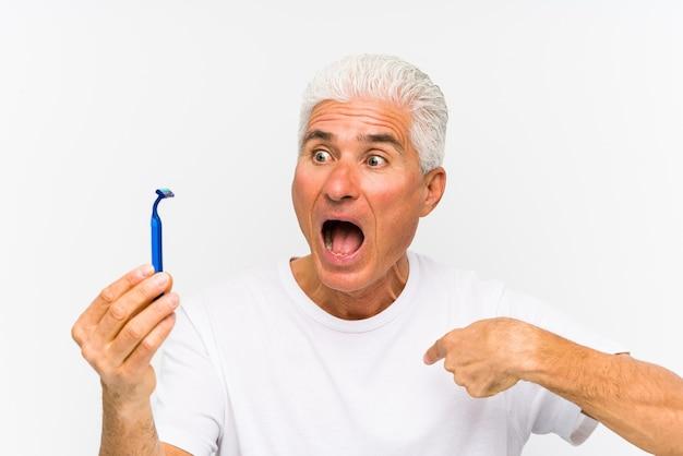 Senior uomo caucasico in possesso di una lama di rasoio isolato ã§surprised indicando se stesso, sorridendo ampiamente. Foto Premium