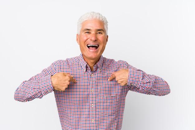 Senior uomo caucasico isolato sorpreso indicando con il dito, sorridendo ampiamente. Foto Premium