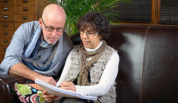 Coppia senior in cerca di un libro su un divano Foto Premium
