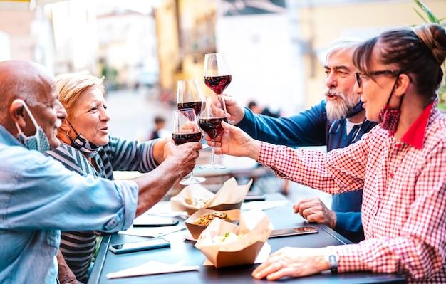 Amici senior che tostano vino rosso al dehor del bar della cantina con maschera facciale aperta Foto Premium