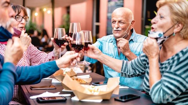 Amici senior che tostano il vino al bar del ristorante che indossa la maschera facciale aperta - concentrarsi sull'uomo calvo Foto Premium
