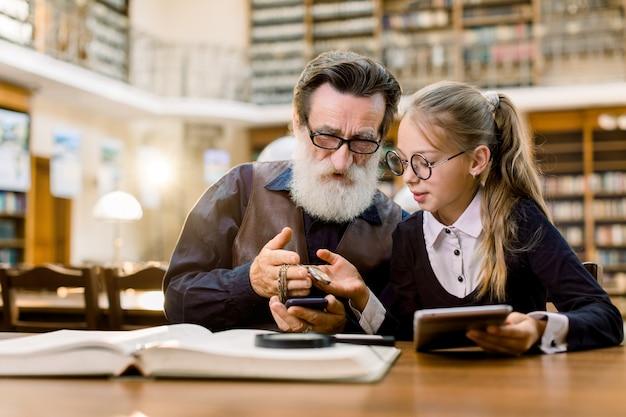 Uomo barbuto bello senior e sua nipote graziosa che esaminano un orologio d'annata su una catena, mentre sedendosi al tavolo con i libri, la compressa e il telefono in vecchia biblioteca. Foto Premium