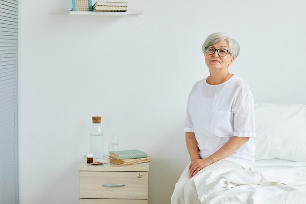 Signora senior che indossa abiti bianchi seduto sul letto nella stanza del reparto ospedaliero Foto Premium