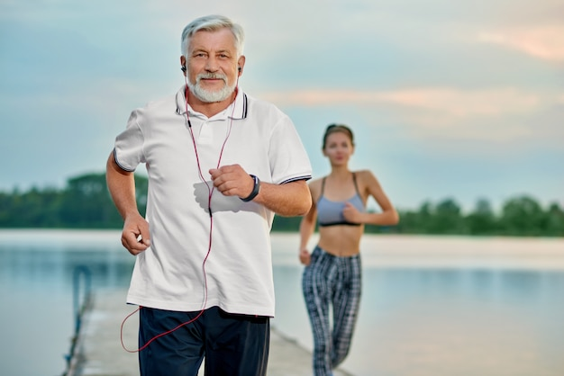 Uomo anziano ascoltando musica, correndo vicino al lago la sera. Foto Premium