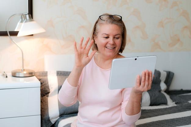 Senior donna in abbigliamento casual guardando la tavoletta digitale e sorridendo alla sua famiglia di amici e agita la mano mentre è seduto a casa Foto Premium