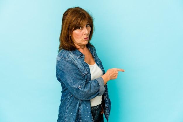 Senior donna isolata sorridendo e indicando da parte, mostrando qualcosa in uno spazio vuoto Foto Premium