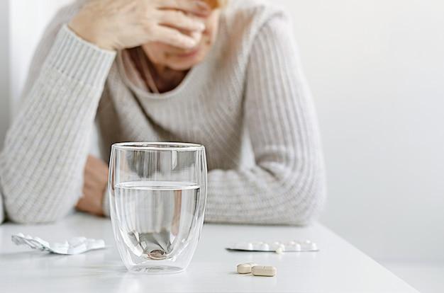 Donna senior che soffre e che prende le pillole dall'emicrania. concetto di trattamento mal di testa. Foto Premium