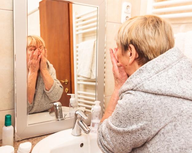 Donna maggiore che tocca la sua pelle morbida viso Foto Premium
