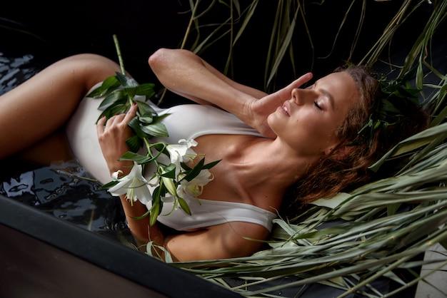 La sensuale ragazza seducente in costume da bagno bianco con fiori di giglio in mano giace in un bagno in stile loft nero pieno d'acqua e con una canna asciutta Foto Premium