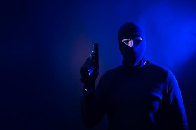 Serie di un ladro caucasico che irrompe in una casa con la pistola in mano. include le luci della polizia. Foto Premium