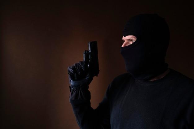 Serie di un ladro caucasico che irrompe in una casa con la pistola in mano. Foto Premium