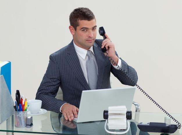 Telefono serio dell'uomo d'affari nel suo ufficio Foto Premium