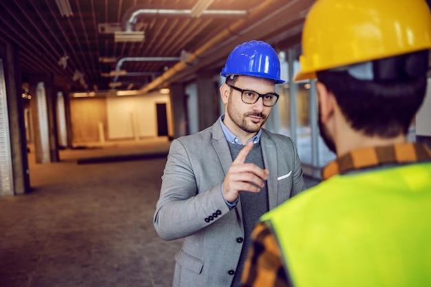 Grave architetto caucasico che attira l'attenzione sull'operaio edile dell'importanza del progetto su cui stanno lavorando. Foto Premium