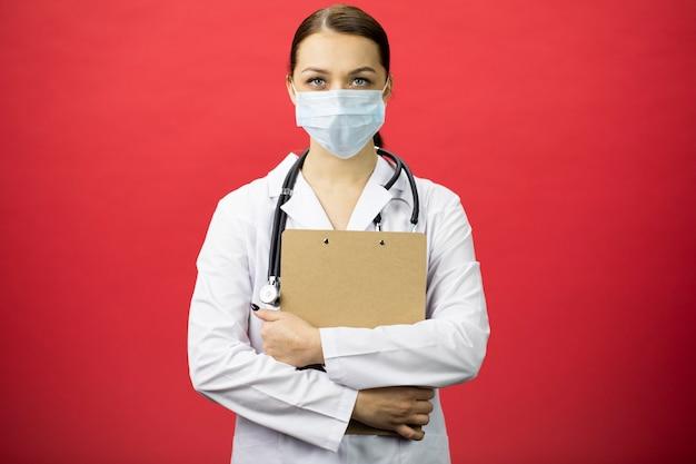 Infermiera femminile seria in lavagna per appunti della tenuta della maschera protettiva in mani Foto Premium