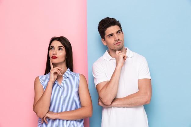 Uomo serio e donna in abbigliamento casual toccando il mento e guardando da parte, isolato su un muro colorato Foto Premium