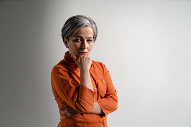 La donna dai capelli grigi matura premurosa seria in camicia arancione che esamina il mento anteriore si è appoggiata sulla mano Foto Premium