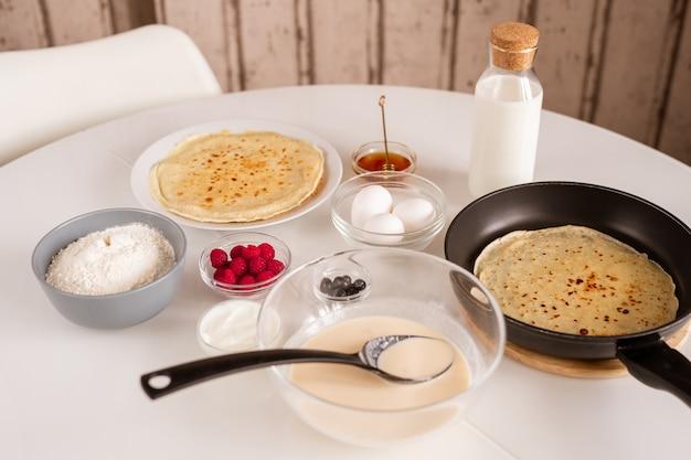 Tavolo da cucina servito con pancake caldo in padella, ciotola con pasta, uova fresche, farina, miele, bottiglia di latte, panna acida, lamponi e more Foto Premium