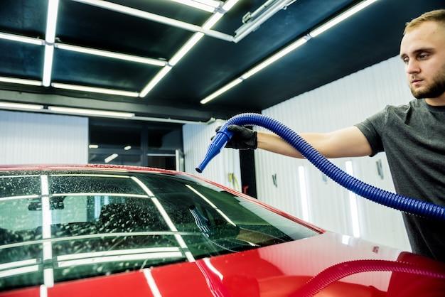 L'addetto all'assistenza effettua l'asciugatura automatica dell'auto dopo il lavaggio. Foto Premium