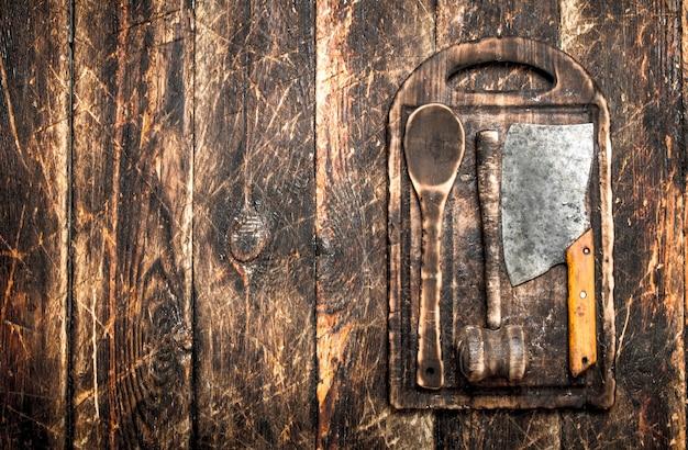 Sfondo di servizio. vecchi utensili da cucina tagliere. su un tavolo di legno. Foto Premium