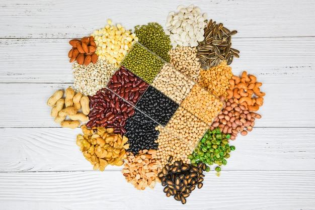 Set di diversi cereali integrali fagioli e legumi semi lenticchie e noci vista dall'alto spuntino colorato - collage vari fagioli mescolano piselli agricoltura di cibo sano naturale per cucinare ingredienti Foto Premium