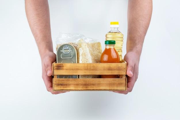 Un set di prodotti per la conservazione a lungo termine e le mani degli uomini su un muro bianco. donazioni di cibo o concetto di consegna di cibo Foto Premium